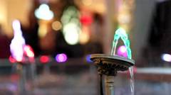 Multicolored fountain jet of water illuminated with colored lights. Stock Footage