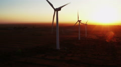 Wind turbines producing renewable green energy in California at sunset - stock footage