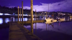 Night Time Scenic Shot Along River Shoreline Of A Boat Dock And Sailboat - stock footage