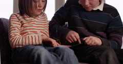 4k, Brother and sister play an online game on their digital touchscreen tablet.  Stock Footage