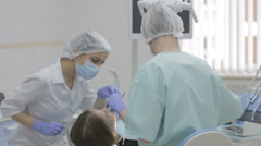 Dentist and dental nurse at work on a reclining patient. Stock Footage