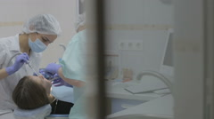 Dentist and dental assistant working on patient's teeth in a real dental surgery Stock Footage