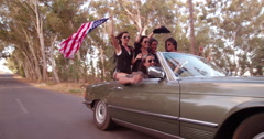 Teenager girl holding an American flag on a road trip - stock footage