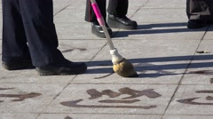 Chinese water calligraphy on a pavement slab. Beijing, China Stock Footage