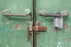 Handles, latch and lock on the metal gate - stock photo