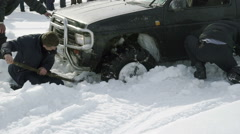 Several men dig the car stuck in the snow - stock footage
