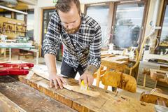 Carpenter works with musical instruments in workshop - stock photo
