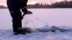 Timelapse video of hauling winter fishing nets at a frozen lake - stock footage