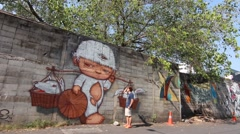 View of street art on the wall in a Soi (lane) of Bangruk area of Bangkok Stock Footage