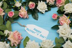 Mothers day card and  beautiful roses on blue wooden background - stock photo