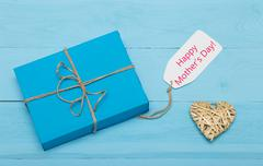 blue gift box with straw heart and mothers day card - stock photo