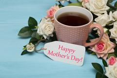 Cup of tea with roses and mothers day tag - stock photo