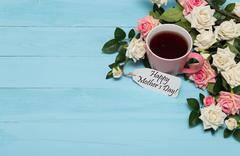 Cup of tea with roses and mothers day tag Stock Photos