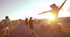 Teenager friends jumping and partying ouside at sunset Stock Footage