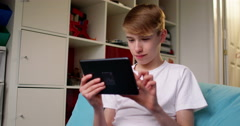 4k, Young boy browsing the internet on a digital tablet at home. Stock Footage