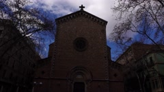 Dark and ominous Gothic church facade against blue sky, dolly motion, slide back - stock footage