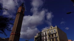 Square Gracia Bell clock tower, tilt down shot, people walk around Stock Footage