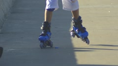 Close-up of legs wearing roller skating shoe, shorts and knee pads, outdoors Stock Footage