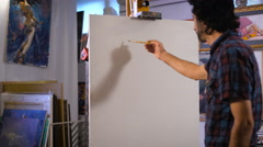 Artist start painting on the canvas which lay on the  tripod paint Stock Footage