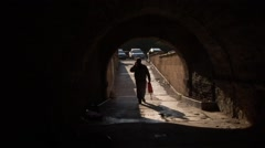 Man walks under semicircular underpass talking on mobile phone - stock footage