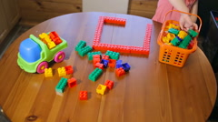 Little girl playing with toy blocks, top view Stock Footage