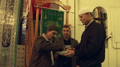 Mufti shares Ramadan holy snacks with Islamic worshippers in mosque - stock footage