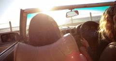 Happy girl friends cheering with raised arms in a convertible - stock footage