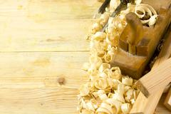 Carpenter tools on wooden table with sawdust. Craftperson workplace top view - stock photo