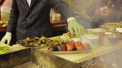 Funny and gallant cook preparing meal at street food fest, gentleman in a suit - stock footage