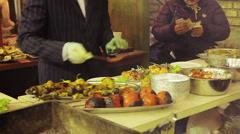 Gentleman cook dressed in a suit preparing meal at street food festival Stock Footage