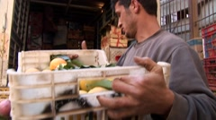 Turkish Cypriot fruit sellers unload oranges from truck for sale in market Stock Footage