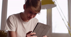 4k, A very happy young boy engrossed in playing games on his digital tablet Stock Footage