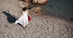 Young brunette woman walking on pebbles along the sea - stock footage