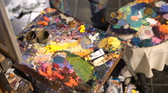 Artist mixes oil paints on pallet with various colors Stock Footage