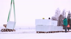 Large ice cube is being loaded on a pallet for transport - stock footage