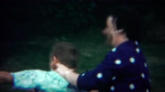 1964: Mother son play wrestling summer outdoor green park. - stock footage