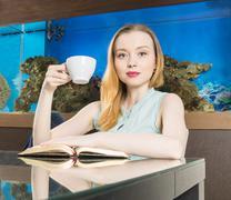 Woman sitting in front of aquarium Stock Photos