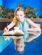 Beautiful woman writing in front of aquarium - stock photo