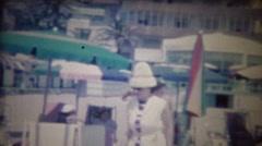 1963: Women funny tall white beach shade hat resort luxury. Stock Footage