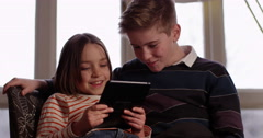 Brother and sister watching an online movie on a digital tablet at hom Stock Footage