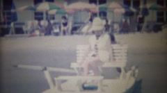 1963: Man pushing lady leisure seated row boat vacation sunshine. - stock footage