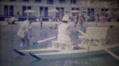 1963: Women rows beach pleasure boat man rides in comfort. Stock Footage