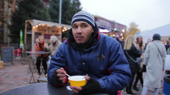 Single guy eating tasty soup outdoors. Rainy weather, sadness, melancholy Arkistovideo