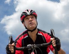 portrait of cyclist at sky background - stock photo