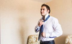 Well dressed business man adjusting his neck tie - stock photo