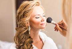 Wedding makeup artist making a make up for bride. Beautiful sexy model girl - stock photo