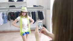 Shopping Mother makes Photo of Daughter using a Mobile Phone in a Clothing Store Stock Footage