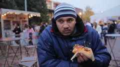 Hungry homeless man eating hot dog outdoors, feeling happy, charity event Stock Footage