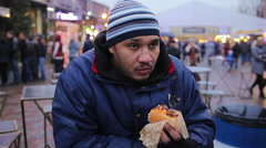 Homeless hungry guy eating hot dog. Charity. Junk food, cholesterol, obesity - stock footage