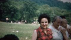 1963: Plaid sleeveless shirt woman outdoor family reunion picnic. - stock footage